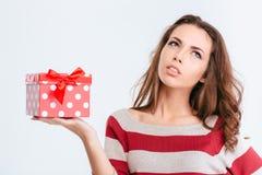 Mujer pensativa joven que sostiene la caja de regalo Fotografía de archivo libre de regalías