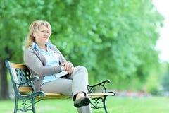 Mujer pensativa madura que se sienta solamente en parque imagenes de archivo