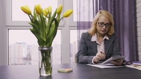 Mujer pensativa mayor que usa la PC de la tableta en el trabajo metrajes