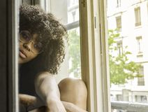 Mujer pensativa negra hermosa joven que se sienta cerca de la ventana en un humor nostálgico fotografía de archivo