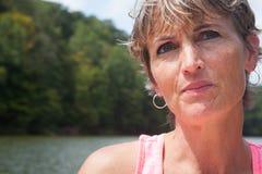 Mujer pensativa por el agua Imagen de archivo libre de regalías