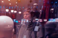 Mujer pensativa que considera a través de ventana de la tienda la noche Imagen de archivo libre de regalías