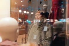 Mujer pensativa que considera a través de ventana de la tienda la noche Fotografía de archivo