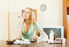 Mujer pensativa que cuenta el coste de medicaciones Fotografía de archivo libre de regalías
