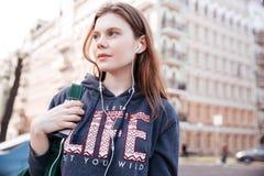 Mujer pensativa que escucha la música del teléfono móvil en la calle Fotografía de archivo