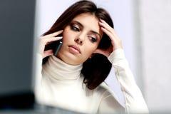 Mujer pensativa que habla en el teléfono Imagen de archivo libre de regalías