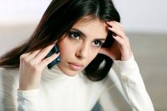 Mujer pensativa que habla en el teléfono Imagen de archivo