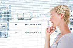 Mujer pensativa que hace una pausa la ventana Imagen de archivo