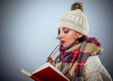 Mujer pensativa que lee un libro Imagen de archivo