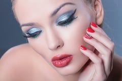 Mujer pensativa que lleva maquillaje agradable y los clavos rojos que miran abajo fotografía de archivo