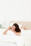 Mujer pensativa que miente en su cama fotografía de archivo