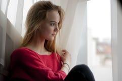 Mujer pensativa que mira hacia fuera la ventana Imagenes de archivo