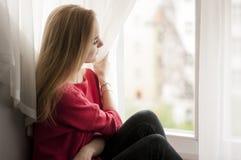 Mujer pensativa que mira hacia fuera la ventana Fotografía de archivo libre de regalías