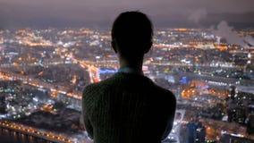 Mujer pensativa que mira la ciudad de la noche del rascacielos almacen de video