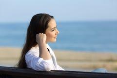 Mujer pensativa que mira lejos en la playa Foto de archivo libre de regalías