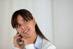 Mujer pensativa que mira para arriba de discurso en el teléfono móvil Imagenes de archivo
