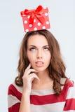 Mujer pensativa que mira para arriba la caja de regalo en la cabeza Foto de archivo libre de regalías