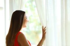 Mujer pensativa que mira a través de una ventana en verano Fotografía de archivo