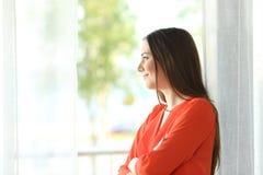 Mujer pensativa que mira a través de ventana Fotografía de archivo libre de regalías