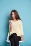 Mujer pensativa que piensa en algo y que mira el smartphone Fotos de archivo libres de regalías