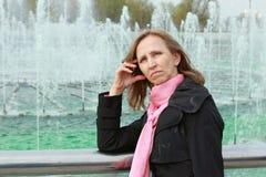 Mujer pensativa que se coloca cerca de una fuente Fotografía de archivo