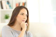 Mujer pensativa que se pregunta en casa Imágenes de archivo libres de regalías