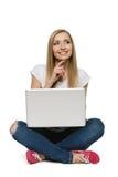 Mujer pensativa que se sienta con la computadora portátil Imagen de archivo