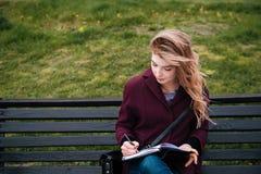Mujer pensativa que se sienta en banco y que escribe en cuaderno al aire libre Fotos de archivo
