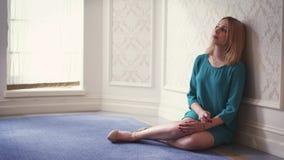Mujer pensativa que se sienta en el piso que se inclina en la pared en ventana ligera del sitio casi almacen de metraje de vídeo