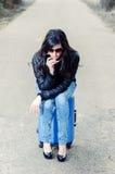 Mujer pensativa que se sienta en la maleta Imagenes de archivo