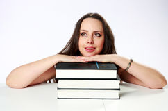 Mujer pensativa que se sienta en la tabla con los libros Imágenes de archivo libres de regalías