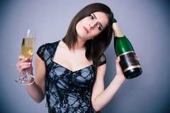 Mujer pensativa que sostiene dos de cristal y la botella de champán Imagen de archivo