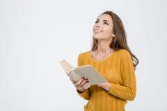 Mujer pensativa que sostiene el libro y que mira para arriba Imagen de archivo libre de regalías