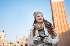 Mujer pensativa que sostiene la cámara delante de Campanile di San Marco Foto de archivo libre de regalías