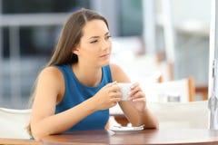 Mujer pensativa que sostiene una taza de café en una barra Imágenes de archivo libres de regalías