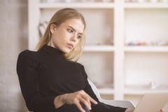 Mujer pensativa que usa el ordenador portátil Foto de archivo libre de regalías