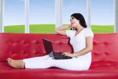 Mujer pensativa que usa el ordenador portátil en casa Imagen de archivo libre de regalías