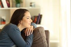 Mujer pensativa satisfecha que mira a través de una ventana fotografía de archivo
