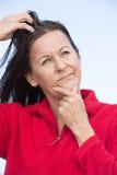 Mujer pensativa subrayada que rasguña la cabeza Foto de archivo libre de regalías