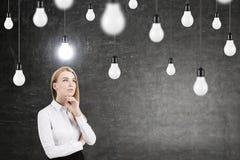 Mujer pensativa y bombillas Imagenes de archivo