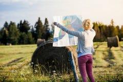Mujer perdida en una escena rural que mira un mapa imágenes de archivo libres de regalías