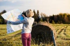 Mujer perdida en una escena rural que mira un mapa Fotos de archivo
