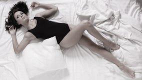 Mujer perezosa de la muchacha atractiva con la almohada en cama en dormitorio Imagen de archivo