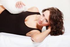 Mujer perezosa de la muchacha atractiva con la almohada en cama en dormitorio Imágenes de archivo libres de regalías