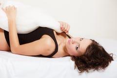 Mujer perezosa de la muchacha atractiva con la almohada en cama en dormitorio Foto de archivo libre de regalías