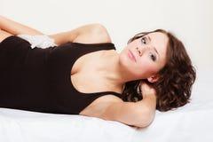 Mujer perezosa de la muchacha atractiva con la almohada en cama en dormitorio Imagenes de archivo