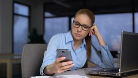 Mujer perezosa que usa el teléfono en vez de hacer el trabajo en el ordenador, concepto del unproductivity almacen de video
