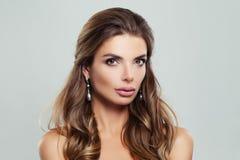 Mujer perfecta con el pelo de Brown y los pendientes ondulados de las perlas Fotos de archivo