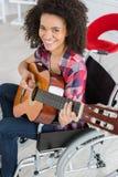 Mujer perjudicada joven que sostiene la guitarra Imágenes de archivo libres de regalías