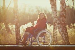Mujer perjudicada sonriente en la silla de ruedas en invierno Fotografía de archivo libre de regalías
